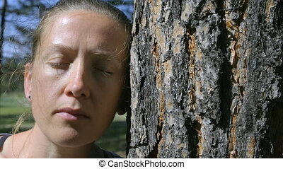 Portrait of a girl with closed eyes, leaning her head against a tree