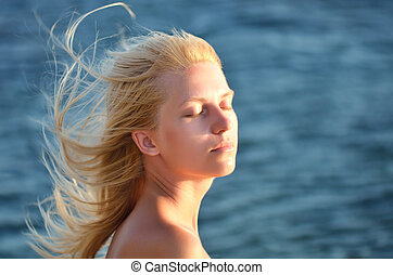Portrait of a girl with eyes closed against the sea