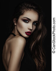 Portrait of a girl with long hair in a low key. Red lips....