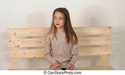 Portrait of a girl with long hair in the Studio, she sits on a wooden bench.