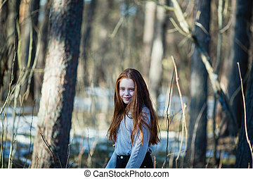 Portrait of a girl with long red hair in the park.