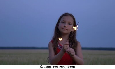Portrait of a girl with sparklers in their hands at evening.