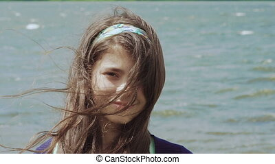 Portrait of a girl with waving hair looking at camera on pool background. Slowly