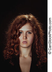portrait of a glamorous young woman on dark background