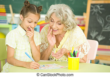 Portrait of a grandmother and granddaughter drawing