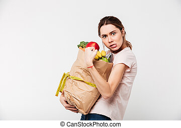 Portrait of a greedy girl holding bag with groceries