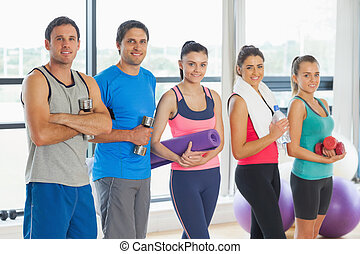 Portrait of a group of fitness class standing in row at a...