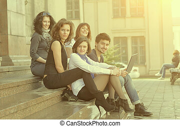 portrait of a group of students sitting in front of the University