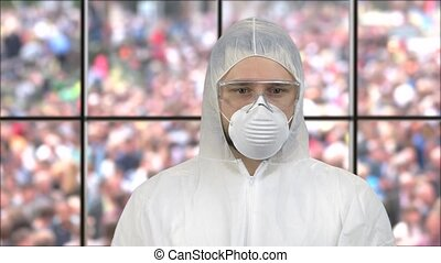 Portrait of a guy wearing white respiratory mask and protective suit. Standing indoors with window view on the crowds.