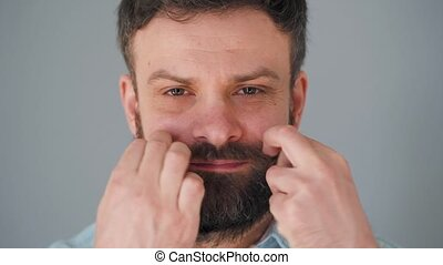 Portrait of a handsome bearded man twists his mustache - ...