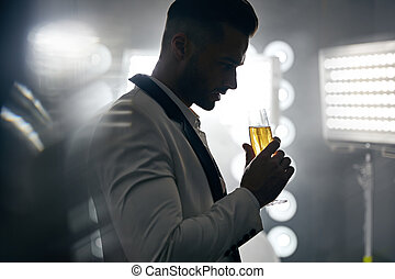 Portrait of a handsome, elegant man drinking champagne