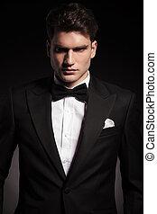 elegant man wearing a black tux. - Portrait of a handsome...