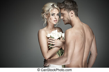 Portrait of a handsome guy with blond womkan holding roses