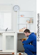 Portrait of a handsome handyman fixing a door