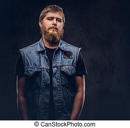 Portrait of a handsome hipster guy dressed in jeans jacket looking at a camera on a dark background.