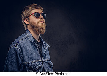 Portrait of a handsome hipster guy dressed in jeans jacket looking away on a dark background.