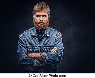 Portrait of a handsome hipster guy dressed in jeans jacket posing with crossed arms on a dark background.