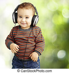 portrait of a handsome kid listening to music and smiling at par