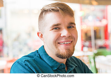 Portrait of a handsome laughing blond man looking to camera...
