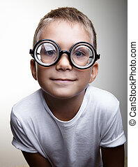 Portrait of a handsome little boy on the white wall background and wearing glasses