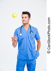 Portrait of a handsome male doctor standing with apple
