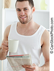 Portrait of a handsome man drinking coffee while reading the news in his kitchen