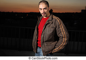 Portrait of a handsome man in brown jacket outdoors