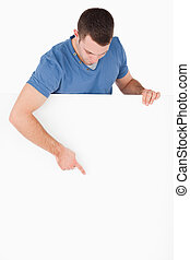 Portrait of a handsome man pointing at a blank panel