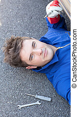 Portrait of a handsome man repairing a car in a garage