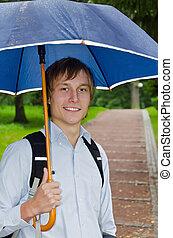 Portrait of a handsome man under umbrella in the park