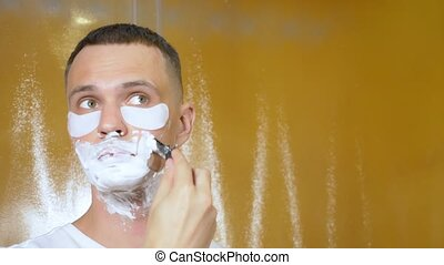 Portrait of a handsome man with eye mask, who shaves with a...