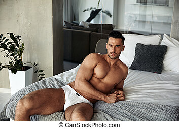 Portrait of a handsome, muscular man relaxing in an apartment