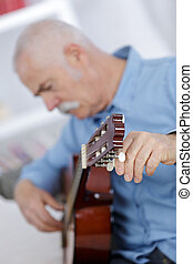 portrait of a handsome senior man playing acoustic guitar