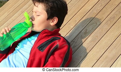 Portrait of a  handsome young boy drinking water from a bottle