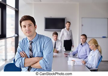 Portrait of a handsome young  business man  on a meeting in offce with colleagues in background