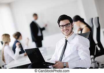 Portrait of a handsome young business man with colleagues in...