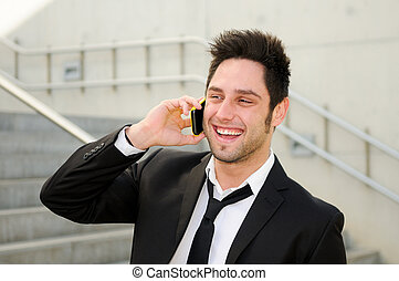 Portrait of a handsome young business man smiling and talking on mobile phone