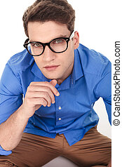 handsome young fashion man sitting on isolated background