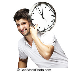 portrait of a handsome young man carrying a clock against a ...