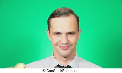 Portrait of a handsome young man holding a coin bitcoin in his hand. Focus on the face. green background, 4k, slow motion
