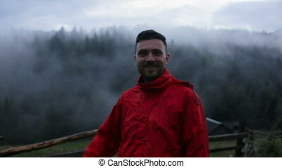 Portrait of a handsome young man in the evening in the mountains