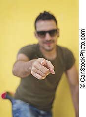 Portrait of a handsome young man pointing finger at you against