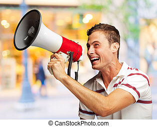 Portrait Of A Handsome Young Man Shouting With Megaphone