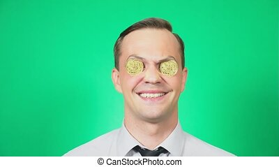 Portrait of a handsome young man with a coin bitcoin in front of eyes. He shows a thumbs-up, a super sign. Focus on the face. green background, 4k, slow motion