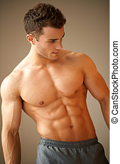 Portrait of a handsome young man with great physique posing...