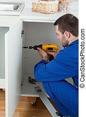 Portrait of a handyman fixing a door