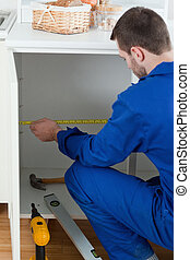 Portrait of a handyman measuring something