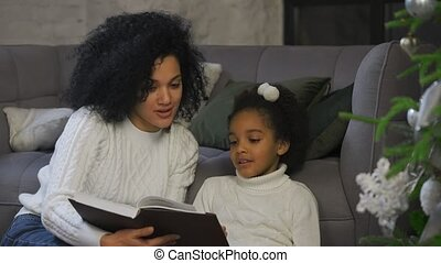 Portrait of a happy African American mom reading a fairy tale to her little daughter. Woman and girl sitting near sofa and decorated Christmas tree against the background of loft style home room. Happy family evening, New Years celebration concept. Close up. Slow motion.