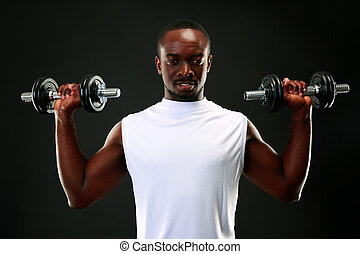 Portrait of a happy african man with dumbbells over black background