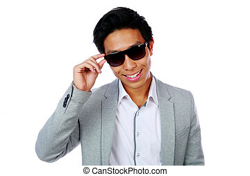 Portrait of a happy asian man in sunglasses over white background